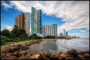 Bocagrande (big mouth) beach in Cartagena. This is the view when you walk from the old, walled city towards the hotels and apartment buildings in Bocagrande. HDR of three handheld shots processed using Photomatix 4 beta. The challenge here is that Photomatix made the rocks way too red, so used Viveza 2 to cool them down, although they still don't look like the real rocks. I decided to use the Photomatix image because the RAW where the rocks are well exposed has a white sky. Played with Viveza to brightenthe buildings, and Tonal Contrast on the buildings and rocks, not the clouds. Also used unsharp mask with radius 1.5 to increase the sharpness of the buildings.